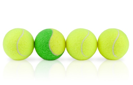 lined up: Four tennis balls lined up on white background with a reflection