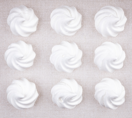 Top view of nine white meringue cookies lying on cross stiched fabric background
