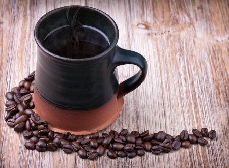 Freshly prepared cup of black coffee with roasted coffee beans on wooden vintage table photo