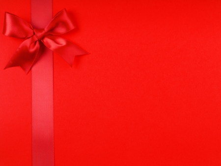 A red ribbon bows on bright red  background photo