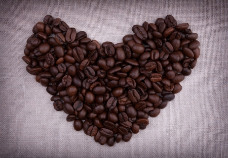 Dark roasted coffee beans  in the shape of a heart on fabric background photo