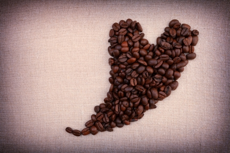 Dark roasted coffee beans  in the shape of a heart on fabric background Stock Photo - 17679909