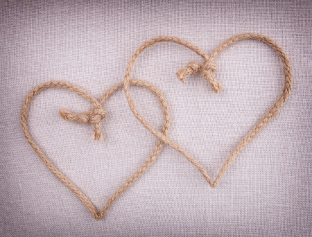string together: Two love hearts  made of string crossed together on fabric vintage background