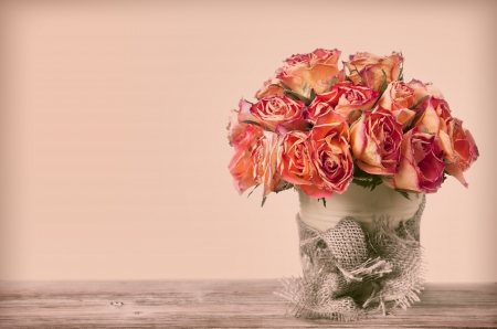 A bouquet of vintage roses in a flower pot decorated with old fabric on wooden surface  Copy space for your text