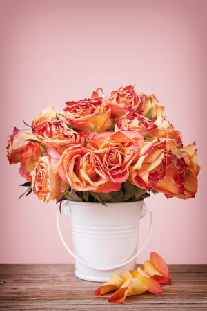 A bouquet of vintage roses in a white metal pot on wooden surface on pink background photo