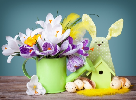 Crocus flowers in  watering can with easter eggs and decoration  photo