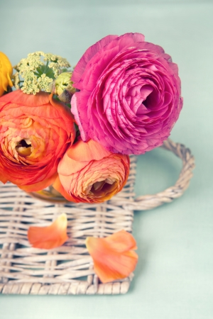 Colorful ranunculus flower on a wicker tray on vintage background photo