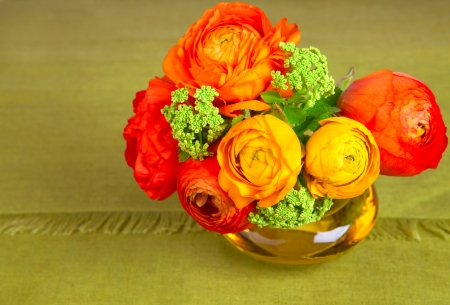 Bouquet of beautiful ranunculus flower in an yellow vase photo