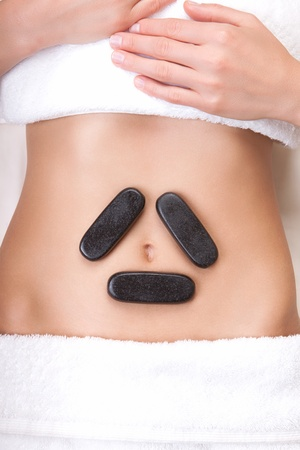triangle shape: Hot stones on a womans tummy in a triangle shape around the belly button Stock Photo