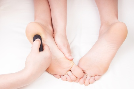 Therapist doing a foot massage, pressing reflexology zone on womans heel with a hot stone photo