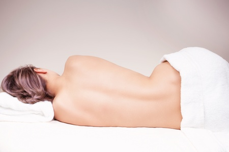 Relaxed woman lying on the massage table in a spa salon