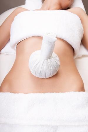 Thai herbal ball on a womans tummy Stock Photo - 20048236