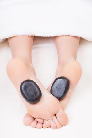 Hot stone reflexology feet massage Standard-Bild