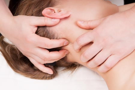 A woman getting a stress relieving pressure point massage on her neck by a therapist