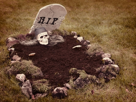 zombie hand: Skull with hands reaching from the grave  Decoration in a garden for halloween