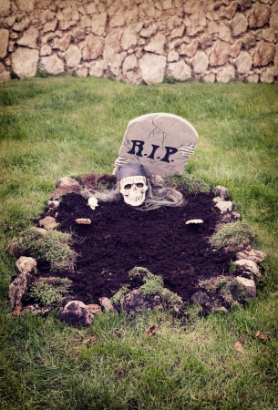 Skull with hands reaching from the grave  Decoration in a garden for halloween photo