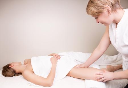 Qualifizierte Therapeuten massiert Frau Bein der Innenseite des Oberschenkels auf der Adduktoren