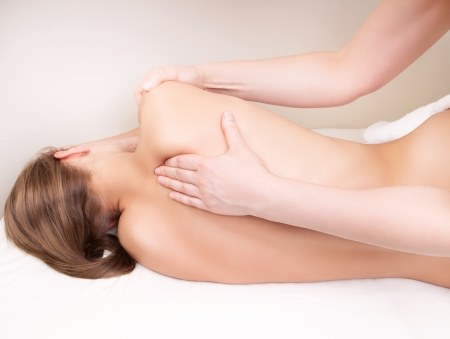 therapeutic massage: Qualified therapist massaging womans shoulder blade Stock Photo