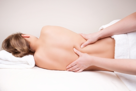 Deep tissue massage on the womans middle back on erector spinae muscles