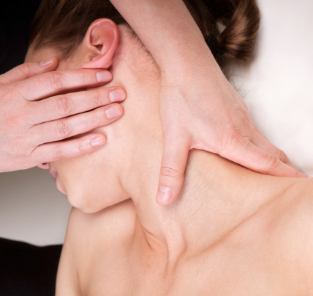 qualified: A woman getting relaxing massage on trapezius muscles of the neck by a qualified therapist