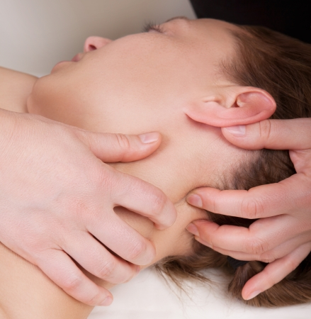 A woman getting a stress relieving pressure point massage on her neck by a health therapist Standard-Bild