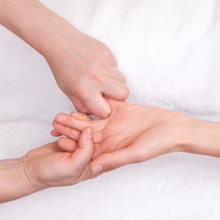 Spa therapist doing relaxing massage on a womans little finger Stock Photo