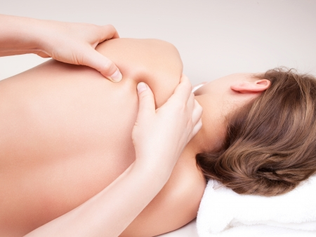 Massage therapy: Deep tissue massage on a womans  shoulder blade  Stock Photo