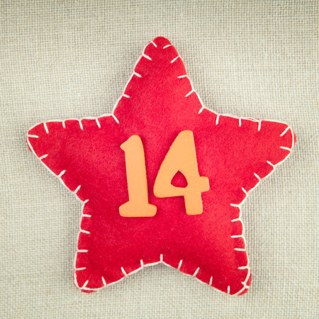 number 14: Red star with wooden number 14 on vintage fabric background