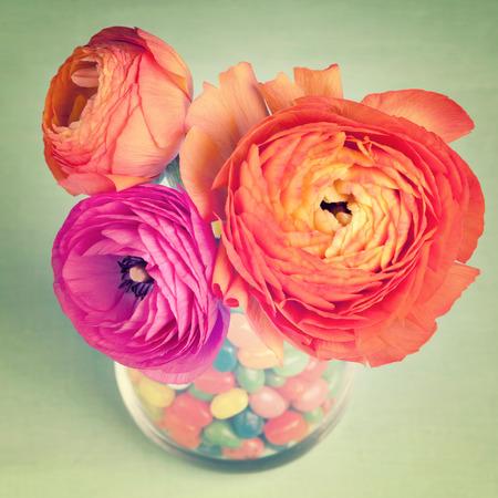 fondo vintage azul: Ran�nculos colorido rosa y naranja en un jarr�n decorado por unos dulces sobre fondo azul de la vendimia