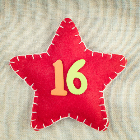 number 16: Red star with wooden number 16 on vintage fabric background