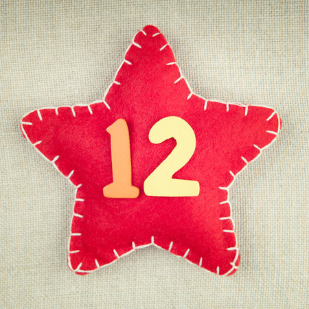 number 12: Red star with wooden number 12 on vintage fabric background