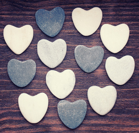 Twelve stone hearts placed nicely on a vintage wood background photo