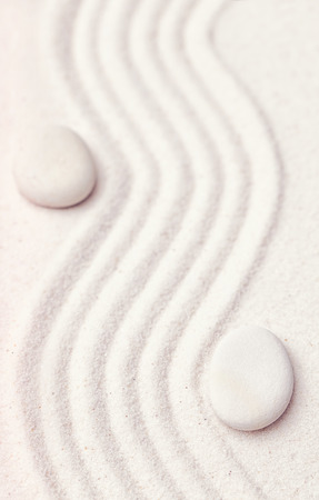 Zen garden with a wave lines in the sand with relaxing white stones