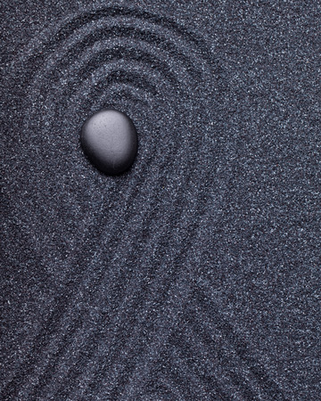 Zen garden with a black stone with wave patterns in the sand surrounding the stone Stock Photo