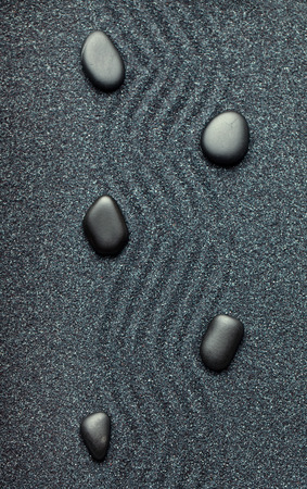 Zen garden with a wave lines in the sand with relaxing black stones