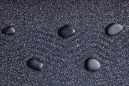Zen garden with a wave lines in the sand with relaxing black stones photo