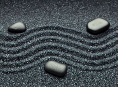 Zen garden with a wave lines in the sand with relaxing massage stones photo