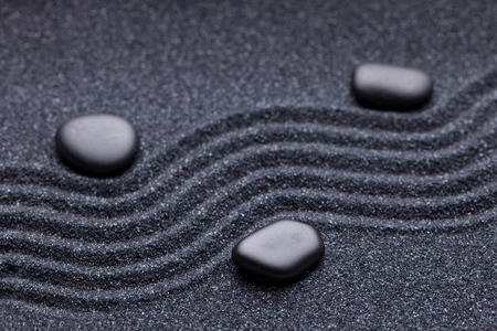 Zen garden with a wave lines in the sand with iregular and relaxing black stones photo