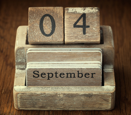 A very old wooden vintage calendar showing the date 4th September on wood background photo