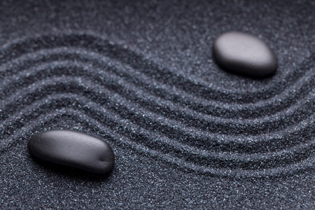 Zen garden with a wave lines in the sand with irregular black stones photo
