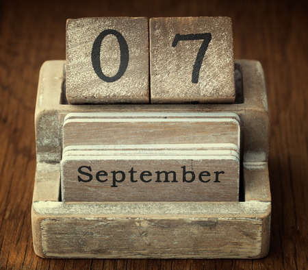 A very old wooden vintage calendar showing the date 7th September on wood background Stock Photo