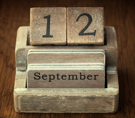 twelve month old: A very old wooden vintage calendar showing the date 12th September on wood background Stock Photo