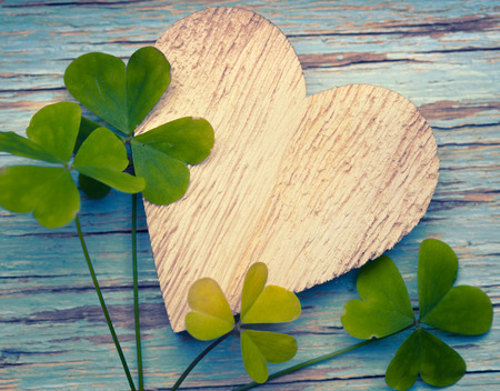 Llucky clovers with an old wooden heart on a blue vintage wood background Standard-Bild