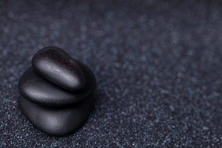 Balancing peaceful black stones in a relaxing zen garden photo