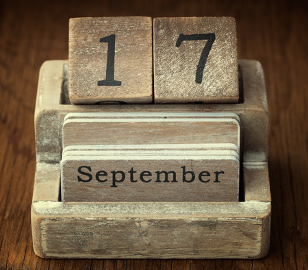 seventieth: A very old wooden vintage calendar showing the date 17th September on wood background