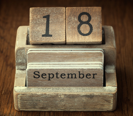 18 year old: A very old wooden vintage calendar showing the date 18th September on wood background Stock Photo