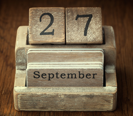 27 years old: A very old wooden vintage calendar showing the date 27th September on wood background Stock Photo