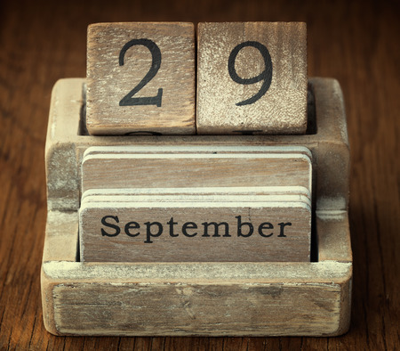 nine years old: A very old wooden vintage calendar showing the date 29th September on wood background Stock Photo