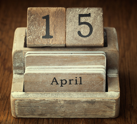 15 months old: A very old wooden vintage calendar showing the date 15th April on wood background Stock Photo