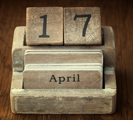 seventieth: A very old wooden vintage calendar showing the date 17th April on wood background Stock Photo